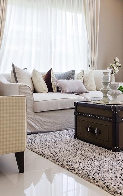Living room with upholstered furniture, window blinds and white net curtain