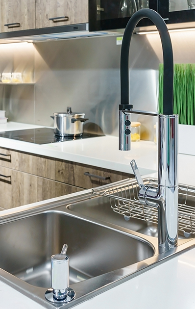 Stainless kitchen sink and Tap water in the kitchen. The interior of the kitchen room of the apartment. Built-In Appliances. Kitchen Appliance. Domestic Appliances